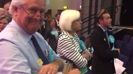 A Brexit Party supporter grins at the camera as others heckle Labour MEP Neena Gill during her accep