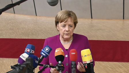 German chancellor Angela Merkel speaks with the media as she arrives for an EU summit. (AP Photo/Ric