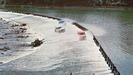 Three Mini Cooper cars crossing a weir over the River Po in Turin in a publicity still issued for th