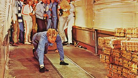 Michael Caine, British actor, wearing blue overalls and crouching down with a stack of gold bullion