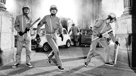 Michael Caine arriving at building with men holding bats in a scene from the film 'The Italian Job',