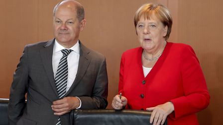 German Finance Minister Olaf Scholz, left, and German Chancellor Angela Merkel, right, arrive for th