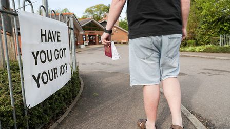 A voter carries his passport along with his poll card to a polling station. Photograph: Andrew Matth