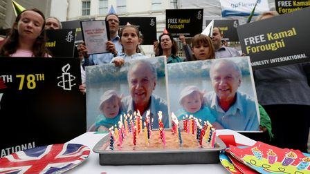 Campaigners stand beside lit candles on a birthday cake outside the Iranian embassy whilst calling u