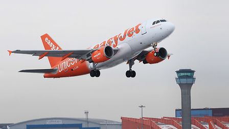 An Easyjet plane takes off from a snowy Luton Airport