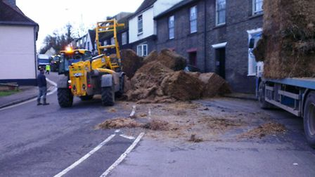 London Road is closed after a trailer fell over shedding its load of hay bales