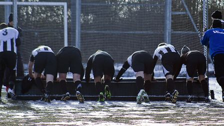MAKING IT CLEAR: St Ives player use a hockey goal to clear the 3G pitch at Comberton on Saturday. Pi