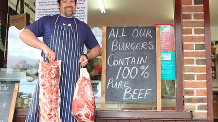 Karl Jelley holding some British beef joints outside his shop in Harpenden