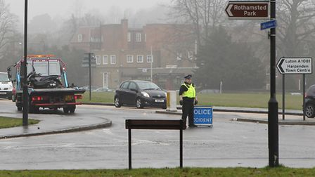 Police close St Albans Road entering Harpenden at the Silver Cup roundabout while a moped is towed a