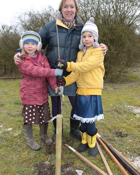 Residents of Heydon, Sarah Scott (middle) with Grace Arthur and Harriet Scott, plant a tree on the o