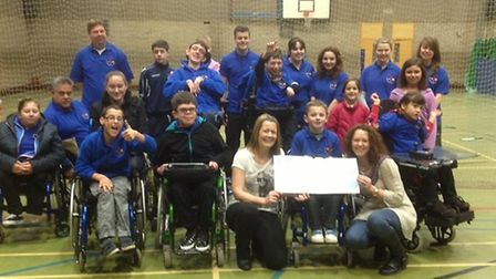 Jo Procter presents a £500 cheque to The Upside Down Sports Club in St Ives.
