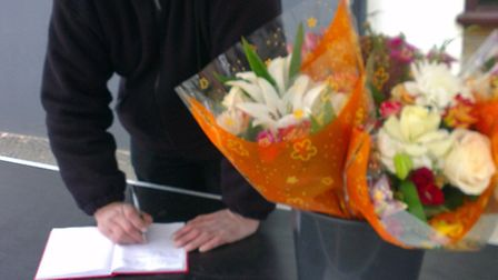 Stallholder Anthony Whiteman with the flowers and book of condolences for John Sims.