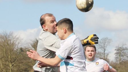 Queens Head Sandridge Res keeper Ian Porter punches clear under pressure from two Nicolas Breakspear