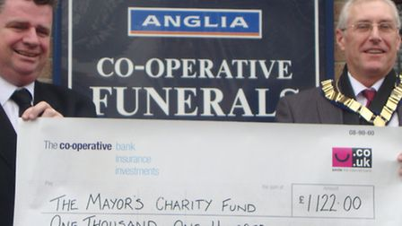 Funeral director Darren Barker presents the £1,122 cheque to Mayor of St Neots Cllr Barry Chapman.