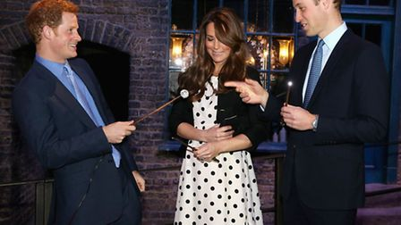 Prince Harry, the Duchess and Duke of Cambridge with their wands on the set used to depict Diagon Al