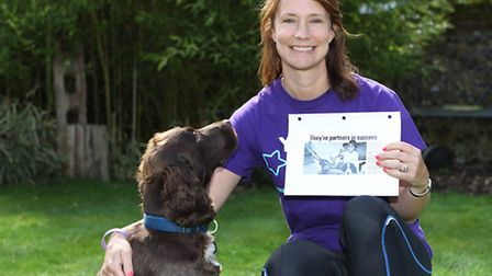 Joanne Gooding with her spaniel Harvey who she has trained with for the London marathon holding a ne