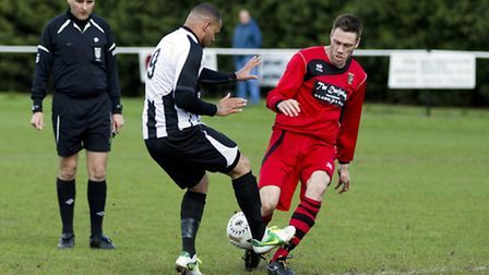 BATTLE LINES: St Ives' Dom Lawless, left, and Huntingdon's Jamie Blackwell clash in the middle of th