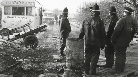 The Hartleys caravan at RAF Molesworth in 1985, watched by police huddling around a brazier