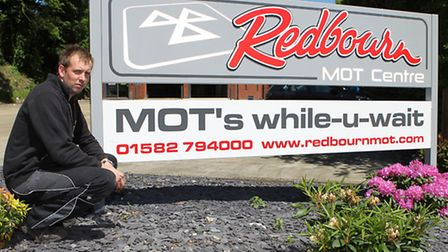 Neal Smith in front of the Redbourn MOT Centre where flowers and shrubs were stolen from the display