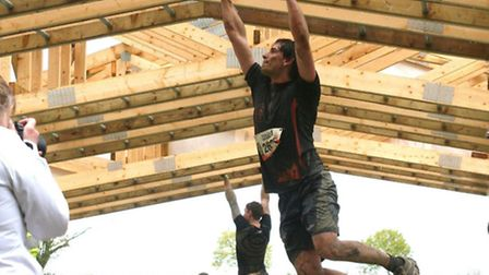 Michael Easton gets to grips with the monkey bars in the Tough Mudder race