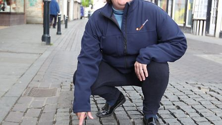 Lisa Thompson shows the damaged cobbles in Royston high Street