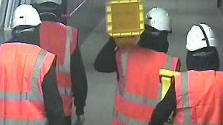 CCTV image of four men dressed in his-vis jackets and hard hats at Radlett station