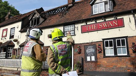 Fire fighters stand outside The Swan pub and assess the damage
