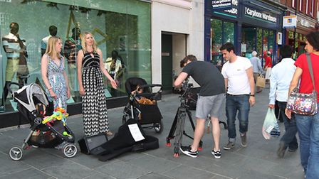Passers by look on as a television crew films the singing mums