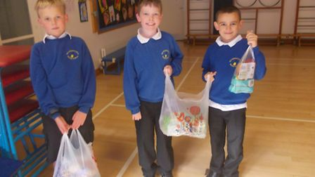 Archie, James and James with Tesco's donation after vandals destroyed the school alottment.