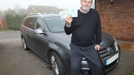 Julian Davis with his car and blue badge parking permit