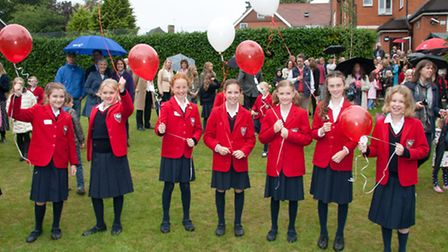 Children prepare to launch balloons to celebrate the opening