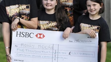 AJS Dance Academy (l-r) Amanda Smith and Rob Smith present a cheque to Molly Moore, with her sister