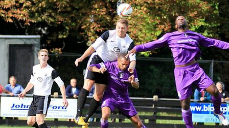 Royston Town's Robbie Mason, pictured in white leaping for the ball, was shown a straight red card a