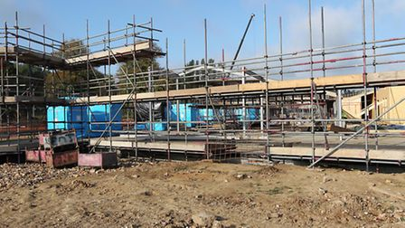 The south side of the new facility with scaffolding surrounding the blue toilet room units which are