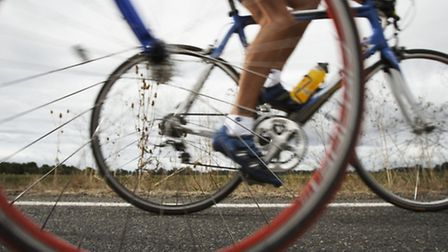 Road cyclist, bicycle wheel in foreground (surface level)