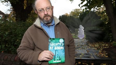 """Author Paul Adams with his book """"Haunted St Albans"""" with a ghostly woman in the background"""