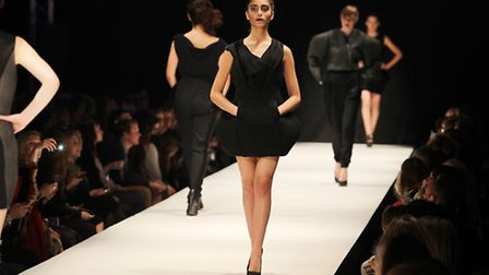 Female models walk down the catwalk wearing black dresses for the fashion show