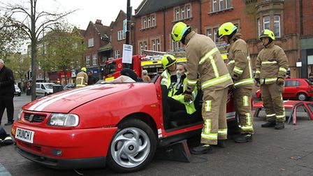 A volunteer sits in the vehicle as the firemen work to remove her safely during a demonstration on S
