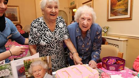 Doris Spencer cuts her birthday cake with sister Olive to celebrate her 100th birthday at Tenterden