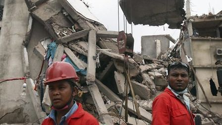 Workers watch as a crane lowers the ceiling of the garment factory building which collapsed in Savar