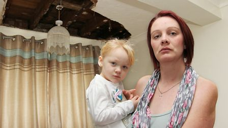Alex Frame with her 3 year old daughter Maisie Ryan in their living room after the ceiling collapsed