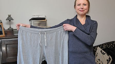 Jan Hopcroft shows off an old pair of trousers since losing 7 stone after joining a local slimming g