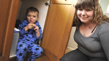 Jaden Gumm, with mum Becky, in the cupboard where he was found.