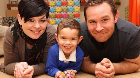"""Amanda and Ross Elliott with Son Max, 3, and his """"Dinosaur Eggs"""" which are stones Max is painting an"""