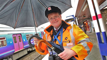 Customer Service Assistant James Allen on the platform with some brollies which he offers to commute