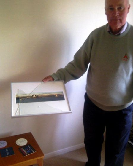 Echo Hill resident Gavin Williams holding the smashed picture frame which came down during the light