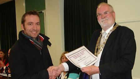 Matthew Hall, chairman of Royston foodbank, receives a grant from Cllr Bob Smith