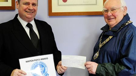 Darren Barker, funeral director for St Neots Co-operative Funerals, presents a cheque for 1,338 to M