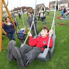 A young disabled boy enjoys a specially designed swing in the new play area