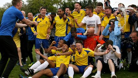 First team coach Harry Wheeler, left, sprays the team with Champagne. Picture: Leigh Page